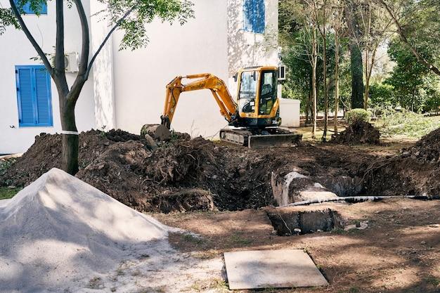 L'escavatore giallo scava il terreno davanti alla casa