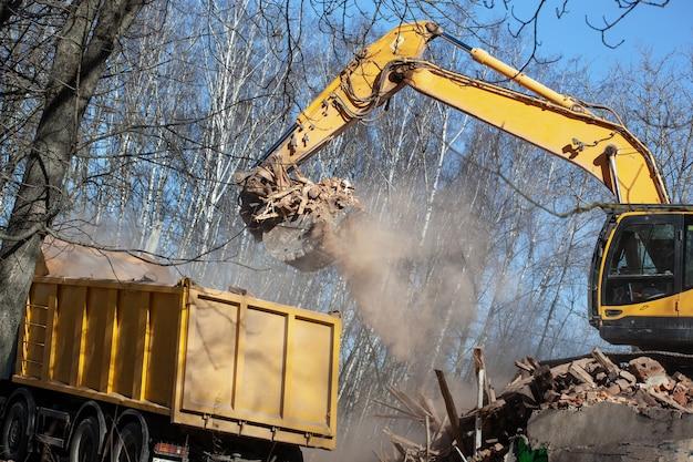 Escavatore giallo che carica un autocarro con cassone ribaltabile con detriti e rifiuti dopo la demolizione dell'edificio