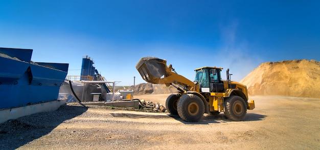 Escavatore giallo durante la pulizia del cortile dello spazio industriale