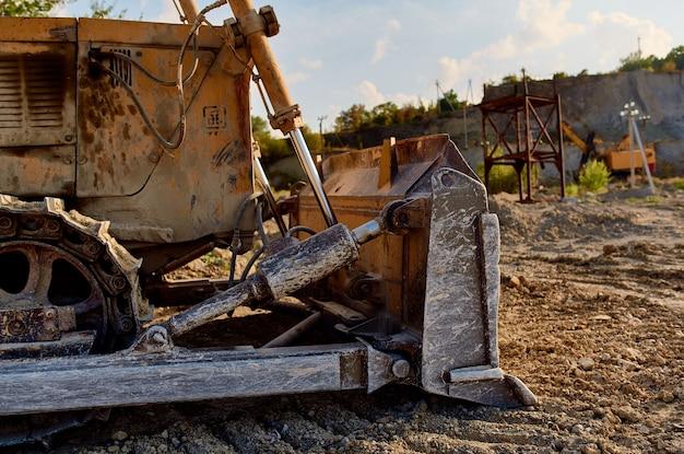 Escavatore giallo con un volante che scava il camion della sabbia estiva a terra.