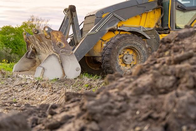 Escavatore giallo. trattore giallo sul campo.