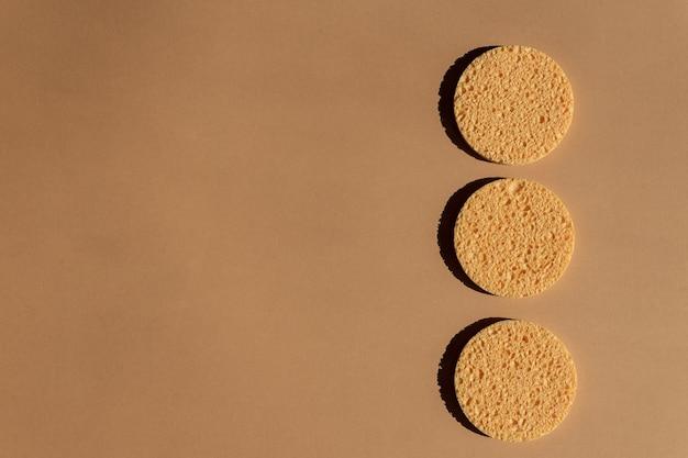 Spugne facciali gialle della cellulosa su fondo marrone. rimozione del trucco, procedure termali a casa.