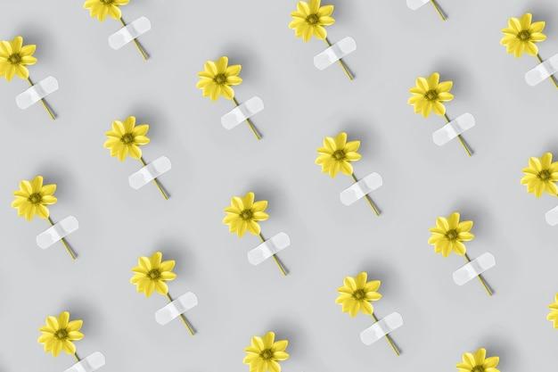 Fiore giallo incollato con cerotto adesivo su grigio