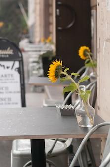 Fiore giallo in un vaso sul tavolo in un caffè all'aperto