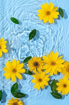 Fiori gialli sulla superficie dell'acqua. bellissimo sfondo di ondulazione dell'acqua per la presentazione del prodotto. copia spazio