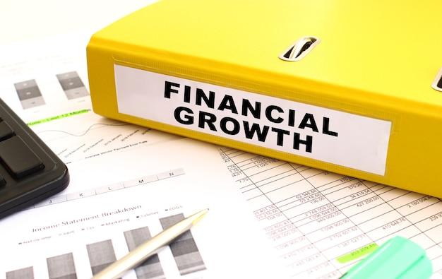 Una cartella gialla con documenti etichettati crescita finanziaria si trova sulla scrivania dell'ufficio con grafici finanziari. concetto finanziario.