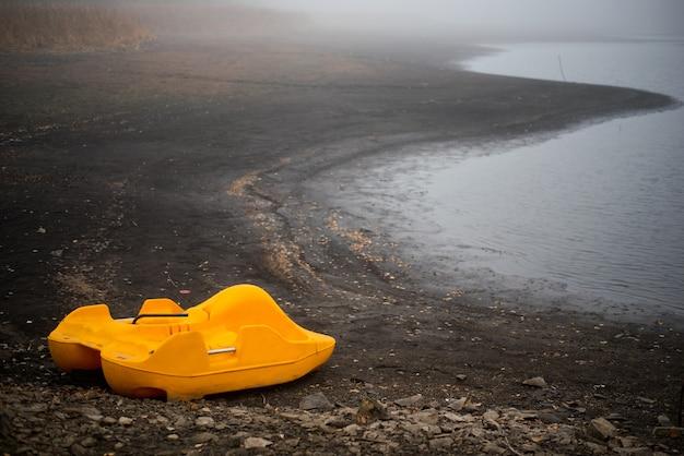 Il catamarano giallo dimenticato si trova da solo sulla costa in autunno