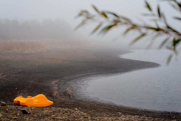 Il catamarano giallo dimenticato si trova da solo sulla riva di un cupo autunno