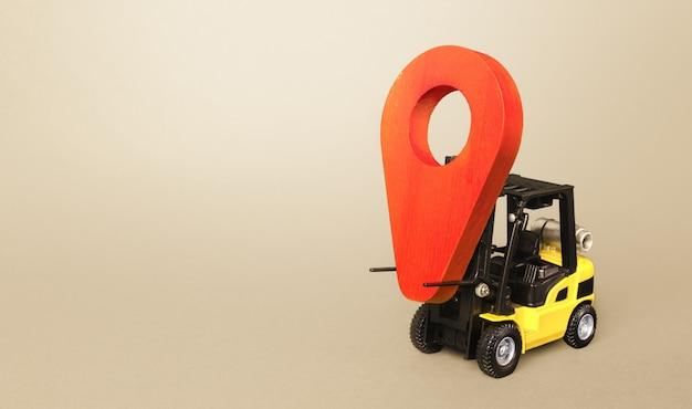 Il carrello elevatore giallo trasporta un indicatore di posizione rosso