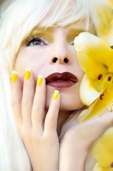 Manicure francese gialla per la ragazza con i gigli gialli in primo piano estivo.