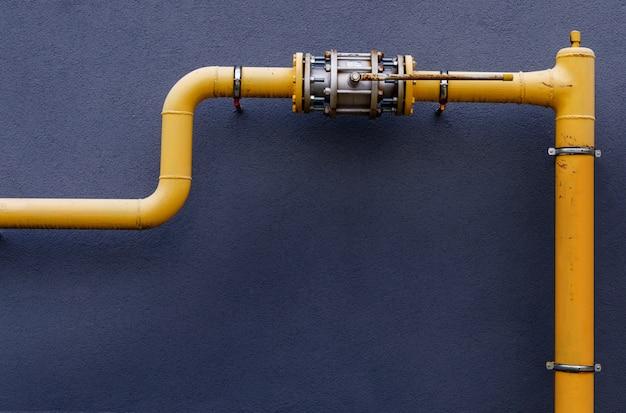 Il tubo del gas giallo con una gru percorre la facciata di un nuovo edificio a più piani.