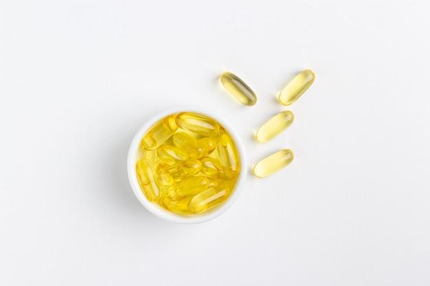 Pillole di olio di pesce gel giallo su sfondo bianco