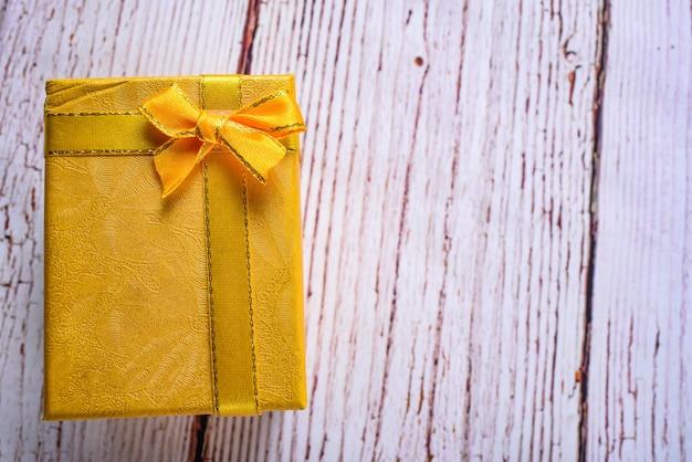 Confezione regalo gialla con nastro di prua sul tavolo di legno bianco, compleanno, concetto di giorno di natale. accettare il concetto di doni