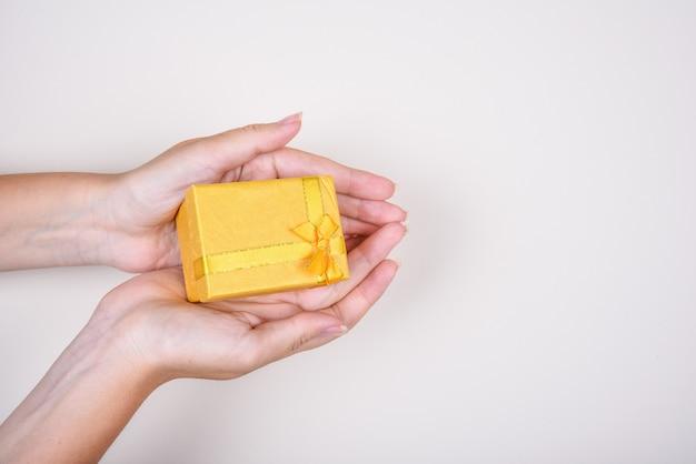 Confezione regalo gialla con nastro di prua nelle mani di donna, compleanno