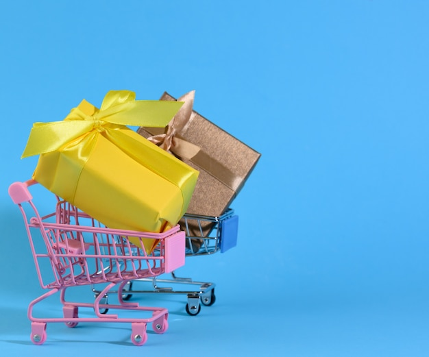 Confezione regalo gialla con fiocco di seta in un carrello di metallo in miniatura su sfondo azzurro. sfondo della festa, sorpresa, vendita stagionale