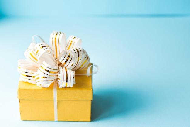 Contenitore di regalo giallo avvolto in nastro a strisce bianco e oro su sfondo blu.