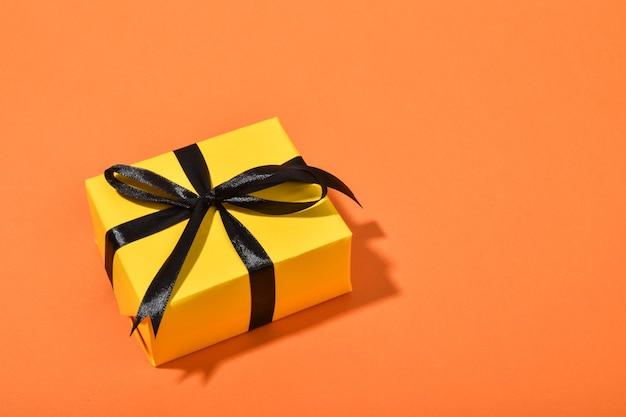 Regalo giallo con un nastro nero su uno sfondo arancione con un posto per il testo