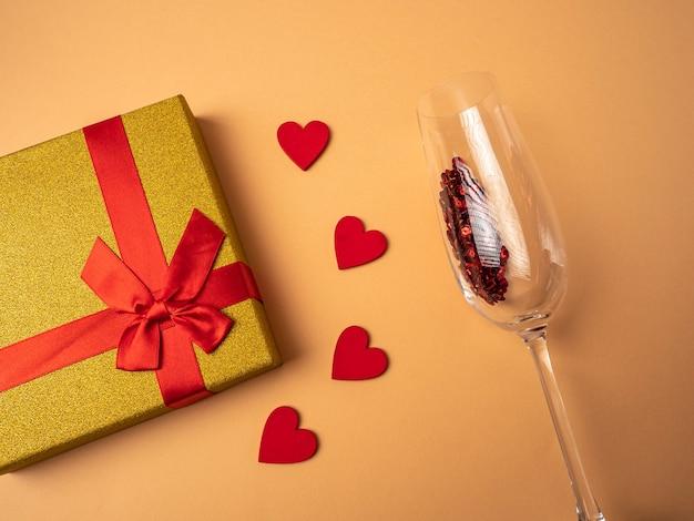 Un regalo giallo con un nastro a forma di nodo a farfalla si trova accanto a quattro cuori rossi e un bicchiere con scintillii rossi su sfondo arancione