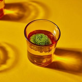Vetro giallo con bellissime ombre profonde con acqua e un bocciolo verde su sfondo arancione