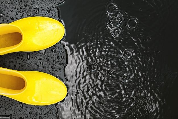 Stivali di gomma lucidi gialli stanno sotto la pioggia sul nero
