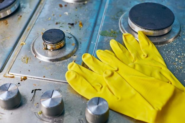 Guanti gialli sul fornello sporco con avanzi di cibo. superficie del piano cottura della cucina in acciaio sporco con macchie di grasso. concetto di pulizia di primavera, rimozione di vecchie macchie di grasso, macchie di frittura e schizzi di olio oil