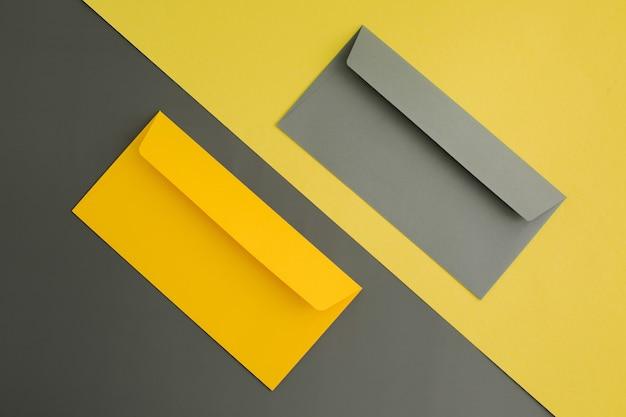 Buste di carta gialle e grigie su sfondo di carta colorata. vista dall'alto.