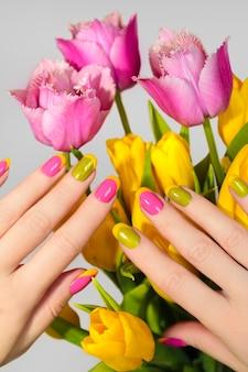 Manicure francese verde giallo con smalto rosa e primo piano dei tulipani