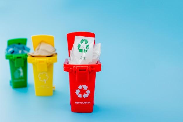 Cestini gialli, verdi e rossi con simbolo di riciclo su sfondo blu. mantieni la città in ordine, lascia il simbolo del riciclaggio. concetto di protezione della natura.