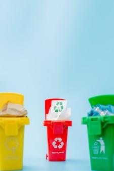 Cestini per il riciclaggio gialli, verdi e rossi con il simbolo del riciclaggio