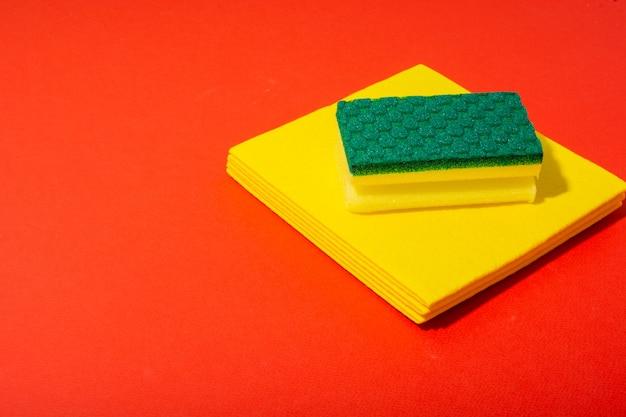 Spugna gialla e verde per pulire e lavare i piatti con un canovaccio giallo
