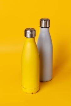 Bottiglie d'acciaio riutilizzabili gialle e grigie su giallo