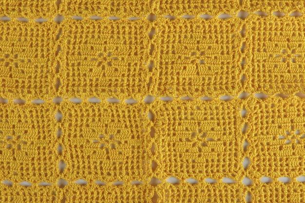Dettaglio di trama all'uncinetto fatto a mano giallo.