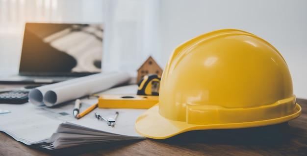 Elmetto di sicurezza giallo con elmetto posizionato sulla scrivania con un piano di progettazione della casa compreso l'equipaggiamento tecnico