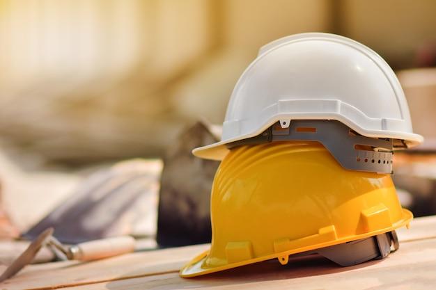 Cappello duro casco giallo sul pavimento di legno nel sito di costrizione