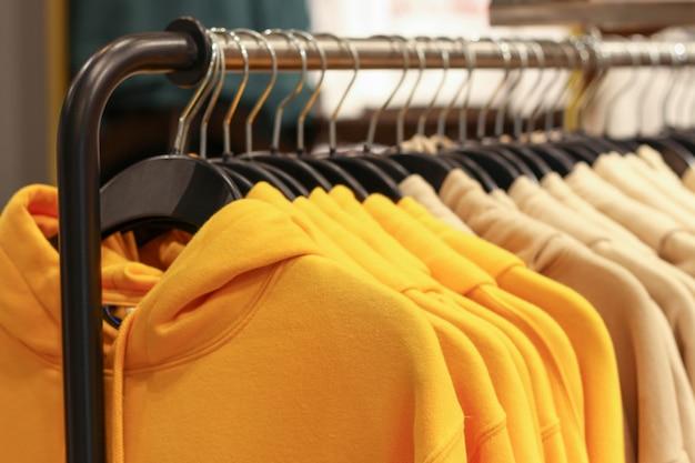 Felpe con cappuccio gialle sui ganci in un primo piano del negozio di articoli sportivi, concetto dell'abbigliamento