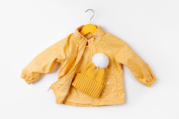 Appendiabiti giallo con cappello su sfondo bianco. simpatico vestito autunnale per bambini.