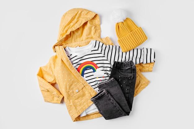 Giacca gialla, jeans e maglione su sfondo bianco. set di vestiti per bambini per l'autunno. vestito alla moda per bambini.