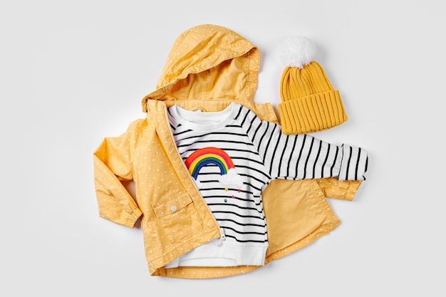 Giacca gialla e maglione a righe su fondo bianco. set di vestiti per bambini per l'autunno. vestito alla moda per bambini.