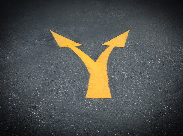 Giunzione direzionale freccia gialla su asfalto