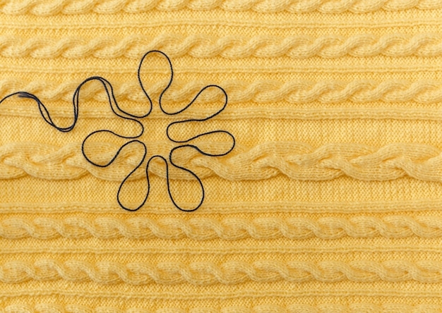 Sfondo giallo lavorato a maglia con motivo e trecce e fantasia fatta a mano floer blu