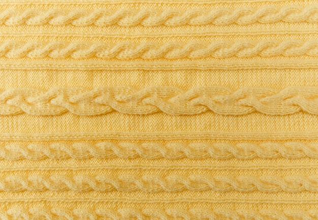 Sfondo giallo lavorato a maglia con fantasia e trecce fatte a mano