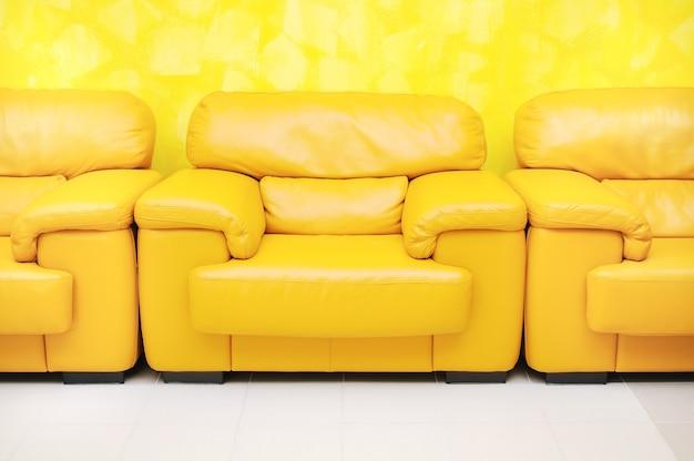 Poltrone in pelle gialla in sala d'attesa e parete testurizzata gialla