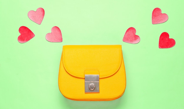 Mini bag in pelle gialla con cuori decorativi su sfondo verde. minimalismo moda e concetto di amore. vista dall'alto