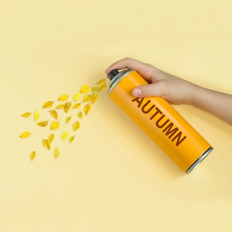 Le foglie gialle volano dalla bomboletta spray con l'iscrizione autunno