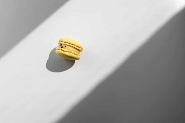 Amaretti francesi di limone giallo o dessert di macarons su sfondo bianco con raggi di luce dalla finestra.