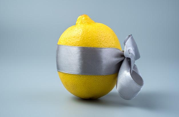 Un limone giallo è legato con un nastro grigio su sfondo grigio.