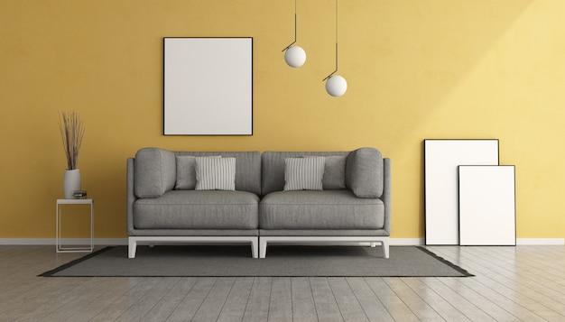 Soggiorno giallo con divano grigio e cornice vuota. rendering 3d