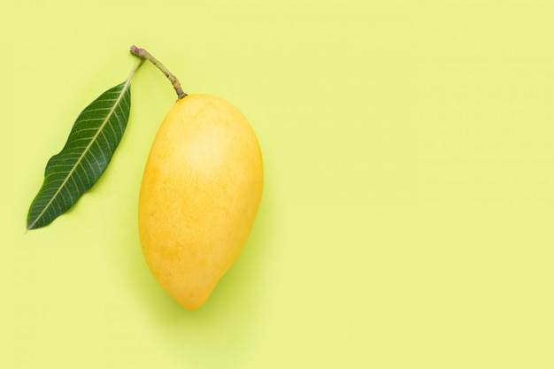 Mango giallo su fondo verde, frutta tropicale succosa e dolce.
