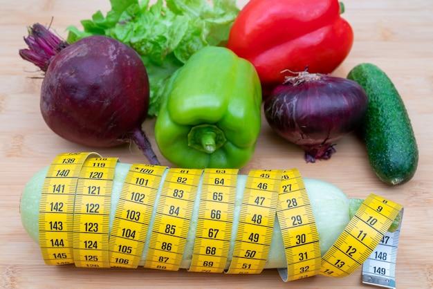 Nastro di misurazione giallo e verdure su un tagliere di legno. dieta stile di vita sano.