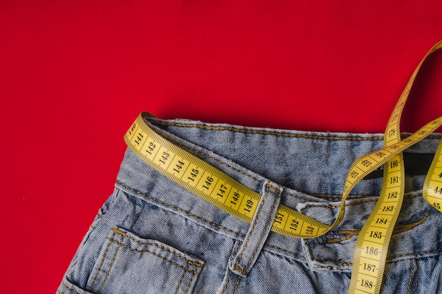 Nastro di misurazione giallo in vita invece di una cintura in jeans su fondo rosso